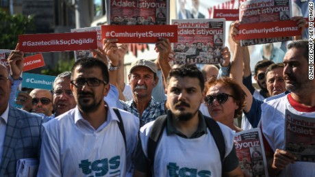 "Reporters hold copies of opposition daily newspaper Cumhuriyet with its frontpage reading ""We want justice"" during a gathering outside the newspapers' headquarters on July 24, 2017 in Istanbul.  Seventeen directors and journalists from one of Turkey's most respected opposition newspapers go on trial on July 24 after spending over eight months behind bars in a case which has raised new alarm over press freedoms under President Recep Tayyip Erdogan. / AFP PHOTO / OZAN KOSE        (Photo credit should read OZAN KOSE/AFP/Getty Images)"