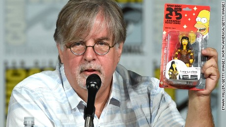 "SAN DIEGO, CA - JULY 11:  Producer/writer Matt Groening gives away a Lucy Lawless figure as he attends ""The Simpsons"" panel during Comic-Con International 2015 at the San Diego Convention Center on July 11, 2015 in San Diego, California."