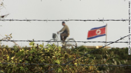 "DANDONG, LIAONING, CHINA - OCTOBER 18:  A North Korean man riding a bicycle near a North Korean flag is seen through the newly installed fence by the Chinese side in this picture taken on October 18, 2006 in the Chinese border city of Dandong, Liaoning Province of China. China urged North Korea not to escalate international tensions, after Pyongyang said the UN resolution imposing sanctions over its nuclear weapons test was a ""declaration of war.""  (Photo by Cancan Chu/Getty Images)"