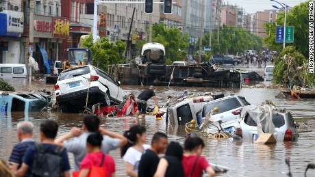 This photo taken on July 14, 2017 shows people looking at submerged cars in a flooded street in Yongji, a county under the administration of the city of Jilin in northeast China's Jilin province. Heavy rains caused flooding that left 18 people dead and another 18 missing around Jilin, with more than 110,000 evacuated when flooding hit the city on July 13 and 14. / AFP PHOTO / STR / China OUT        (Photo credit should read STR/AFP/Getty Images)