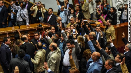 "Opposition deputies raise their hands while voting to open a political trial against President Nicolas Maduro, during a special session of the National Assembly, on October 25, 2016 in Caracas. A majority of lawmakers voted in favor of a motion to launch a ""political and criminal trial"" against Maduro after he blocked their drive for a referendum on removing him. / AFP / JUAN BARRETO        (Photo credit should read JUAN BARRETO/AFP/Getty Images)"