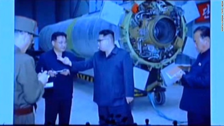 North Korean leader Kim Jong Un standing in front of the Hwasong-10, with the engine visible.
