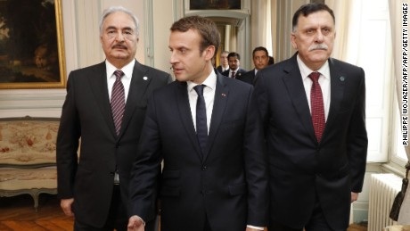 French President Emmanuel Macron (C) walks with Libyan Prime Minister Fayez al-Sarraj (R) and General Khalifa Haftar (L), commander in the Libyan National Army (LNA).