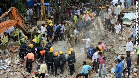Indian rescue workers look for survivors in debris at the site of a building collapse in Mumbai on July 25, 2017. Rescuers were frantically searching for up to 40 people feared trapped in a four-storey building that collapsed July 25 in India's financial capital of Mumbai, officials said. / AFP PHOTO / PUNIT PARANJPE        (Photo credit should read PUNIT PARANJPE/AFP/Getty Images)