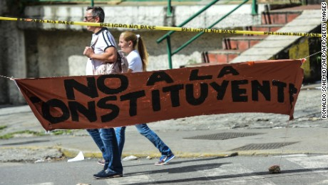 People walk past a banner placed by anti-government activists against President Nicolas Maduro's Constituent Assembly, in Caracas' Petare neighbourhood on July 26, 2017. Venezuelans began blocking off deserted streets Wednesday as the opposition launched a 48-hour general strike aimed at thwarting embattled President Nicolas Maduro's controversial plans to rewrite the country's constitution. / AFP PHOTO / Ronaldo SCHEMIDT        (Photo credit should read RONALDO SCHEMIDT/AFP/Getty Images)