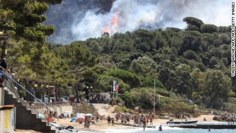Beachgoers in La Croix-Valmer, near Saint-Tropez, watch as the fire spreads.