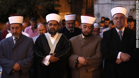 Sheikh Omar Kiswani (2-L), Al-Aqsa director, and other clergymen join as Palestinian Muslim worshippers pray outside Jerusalem's Old City on July 25, 2017 as Muslim officials said worshippers should continue to boycott the Al-Aqsa mosque compound, even after Israel removed newly installed security measures that had triggered deadly violence. Israel removed metal detectors from a highly sensitive Jerusalem holy site after their installation triggered deadly violence, but Muslim officials said worshippers should continue a boycott for now. Israel installed metal detectors at entrances to the compound after an attack nearby that killed two policemen on July 14. / AFP PHOTO / Ahmad GHARABLI        (Photo credit should read AHMAD GHARABLI/AFP/Getty Images)