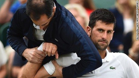 Djokovic receives medical attention on court during his fourth-round match against Adrian Mannarino at Wimbledon.
