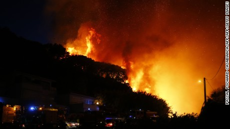 Firefighters gather at the site of a fire in Biguglia, on the French Mediterranean island of Corsica, on July 24, 2017. Dozens of firefighters were battling a blaze on the French island of Corsica on July 24 that has spread across 900 hectares of forest and was threatening homes, emergency services said. Residents were evacuated from homes at the edge of the town of Biguglia, on the island's northeastern coast.  / AFP PHOTO / PASCAL POCHARD-CASABIANCA        (Photo credit should read PASCAL POCHARD-CASABIANCA/AFP/Getty Images)