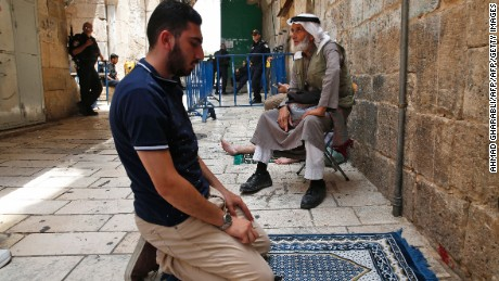 A Palestinian Muslim prays outside the gates of Al-Aqsa mosque compound in the old city of Jerusalem on July 26, 2017, as a tense standoff is underway between Israel and Muslim worshippers at the holy complex, known to Jews as the Temple Mount. Muslims have refused to enter the site and have prayed in the streets outside for more than a week after Israel installed new security measures at the Haram al-Sharif compound, known to Jews as the Temple Mount. / AFP PHOTO / AHMAD GHARABLI        (Photo credit should read AHMAD GHARABLI/AFP/Getty Images)