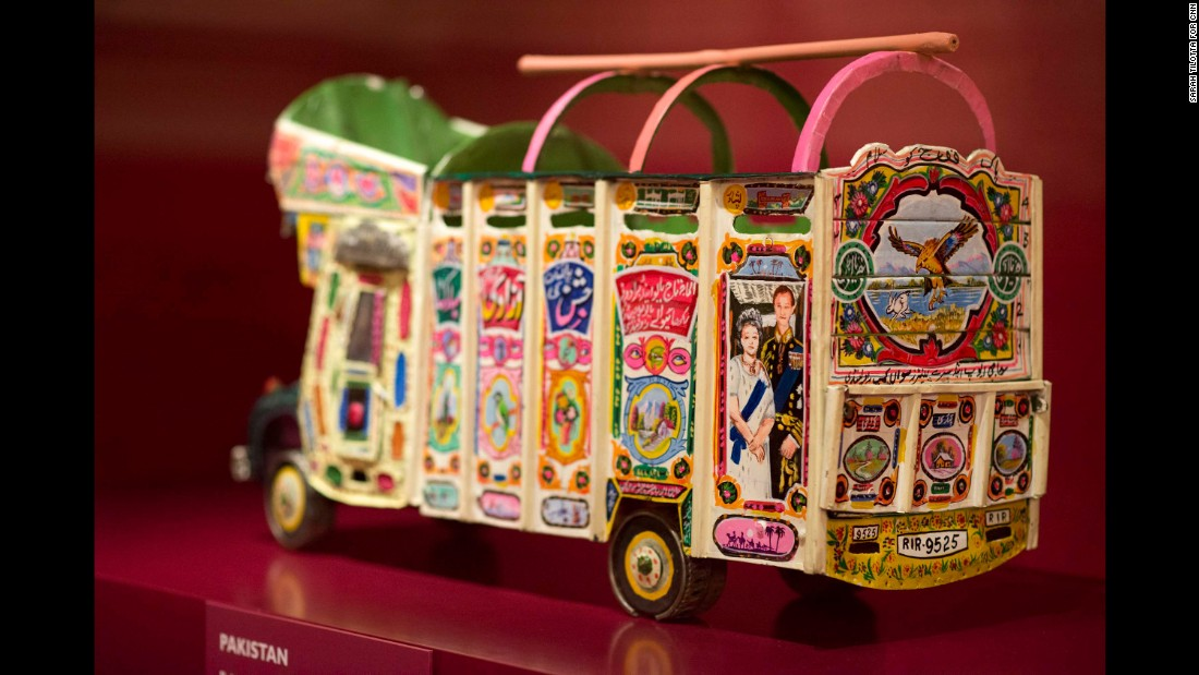 An association of Pakistani drivers presented this brightly colored tin model bus to the Queen and Prince Philip in 1997. It includes a picture of them and the flags of the UK and Pakistan.