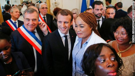 Mayor of Orleans Olivier Carre (L) and French President Emmanuel Macron (C) pose for a group photo with people who received French citizenship.