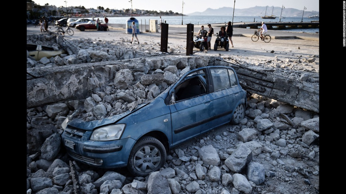 "People on the Greek island of Kos look at a car crushed by rubble after a 6.7 magnitude earthquake <a href=""http://www.cnn.com/2017/07/20/europe/greece-turkey-earthquake/index.html"" target=""_blank"">rocked the island</a> on Friday, July 21."