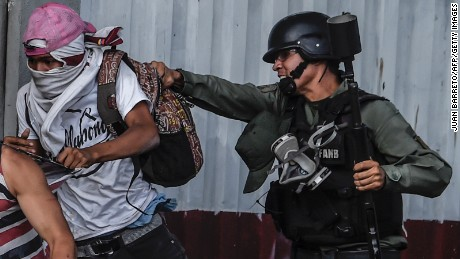 An anti-government activist is grabbed by a member of the National Guard during clashes in Caracas on July 27, 2017 on the second day of a 48-hour general strike called by the opposition. Venezuela's opposition called for a nationwide protest on Friday in outright defiance of a new government ban on demonstrations ahead of a controversial weekend election.