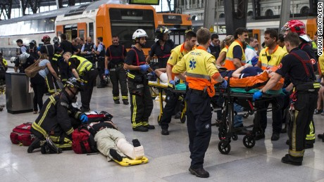 Spanish firefighters and paramedics treat injured people at Francia Railway Station in Barcelona, northeastern Spain, 28 July 2017. According to reports, at least 48 people were wounded, five of them are seriously injured, when a train crashed into the track buffer.