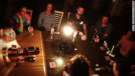 Friends play poker by candlelight after a power outage on Hatteras Island, North Carolina.