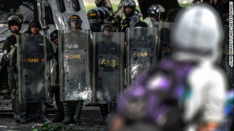 National guard troops in riot gear stand behind shields during a protest Friday in Caracas.