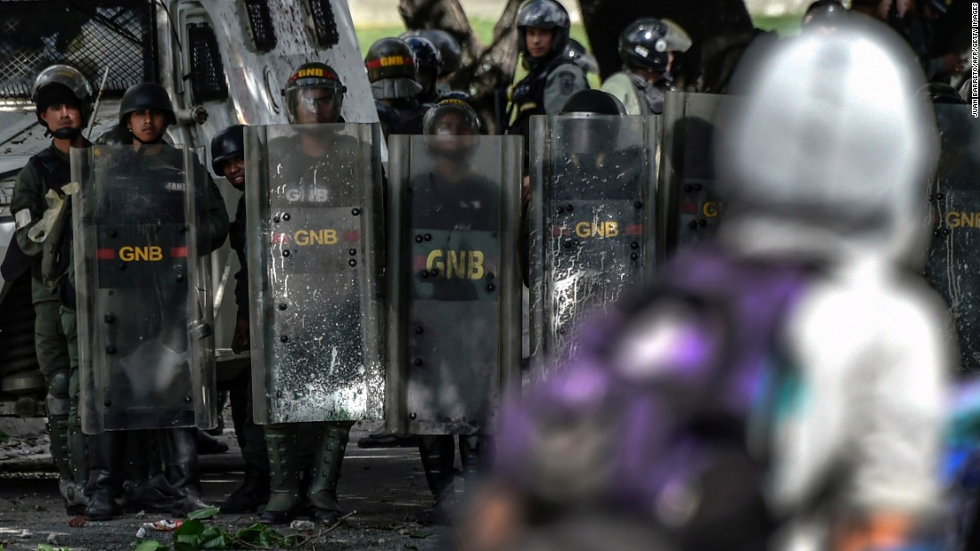 National guard officers use shields to protect themselves during a protest against the Maduro regime July 28 in Caracas.