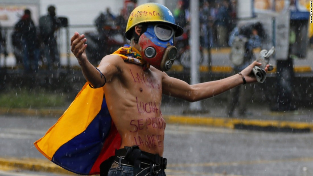 A protester faces off against the national guard during a downpour July 28 in Caracas.