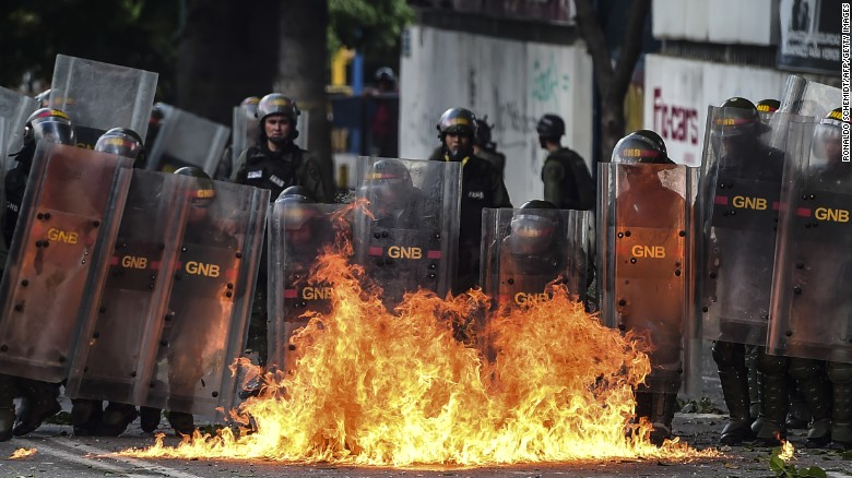 Members of the National Guard use their shields behind a fire during clashes with anti-government demonstrators in Caracas, on July 26, 2017. Venezuelans blocked off deserted streets Wednesday as a 48-hour opposition-led general strike aimed at thwarting embattled President Nicolas Maduro's controversial plans to rewrite the country's constitution got underway. /