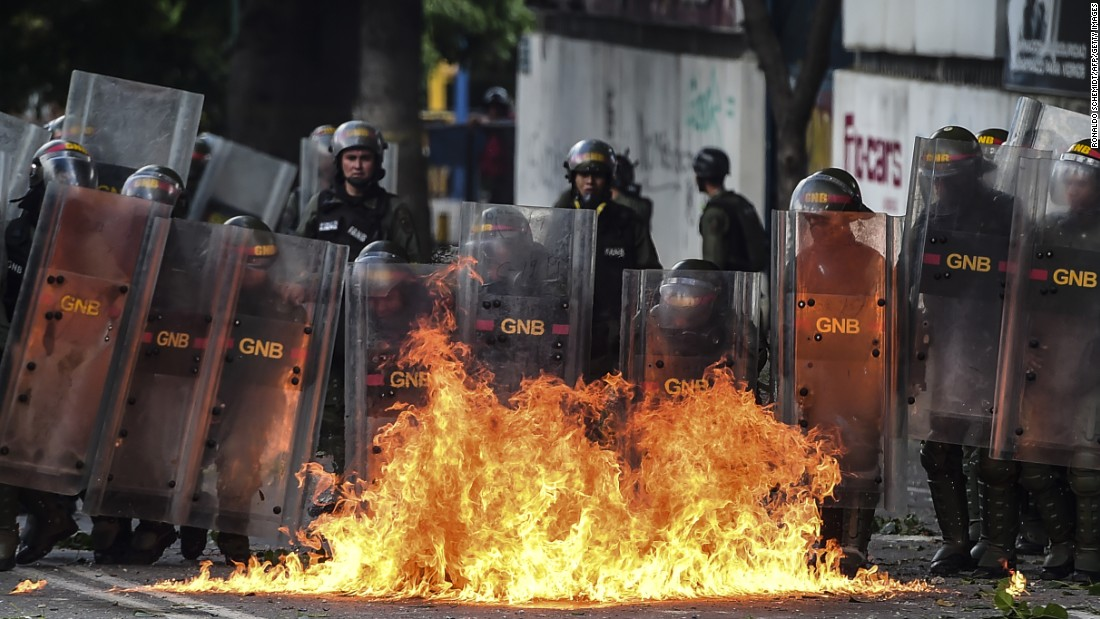 Members of Venezuela's national guard protect themselves in front of a street fire Wednesday, July 26, in Caracas during a two-day, opposition-led general strike.
