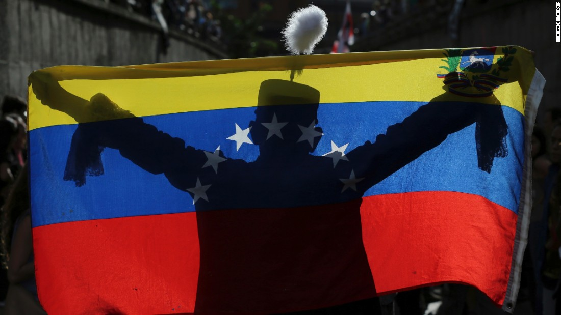 A demonstrator dressed as Venezuelan independence hero Simón Bolívar is silhouetted against a national flag on July 24 in Caracas in tribute to those who have been killed during the crisis. More than 100 people have died in the unrest, the attorney general's office says.