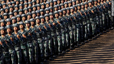 In this photo released by China's Xinhua News Agency, Chinese People's Liberation Army (PLA) troops march in formation Sunday, July 30, 2017 as they arrive for a military parade to commemorate the 90th anniversary of the founding of the PLA on Aug. 1 at Zhurihe training base in north China's Inner Mongolia Autonomous Region. (Ju Zhenhua/Xinhua via AP)