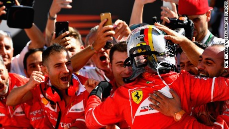 Sebastian Vettel celebrates his Hungary GP win in parc ferme with his Ferrari team.