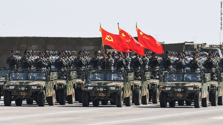 Chinese soldiers carry the flags of the Communist Party and the People's Liberation Army during a military parade in China's northern Inner Mongolia region on July 30, 2017.
