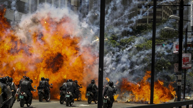 "Members of Venezuela's national police are caught in an explosion as they ride motorcycles near Altamira Square in Caracas on July 30. Venezuela <a href=""http://www.cnn.com/2017/05/09/americas/venezuela-violin-protester/"" target=""_blank"">has seen widespread unrest</a> since March 29, when the Supreme Court dissolved Parliament and transferred all legislative powers to itself. The decision was later reversed, but protests have continued across the country, which is also in the midst of an economic crisis."