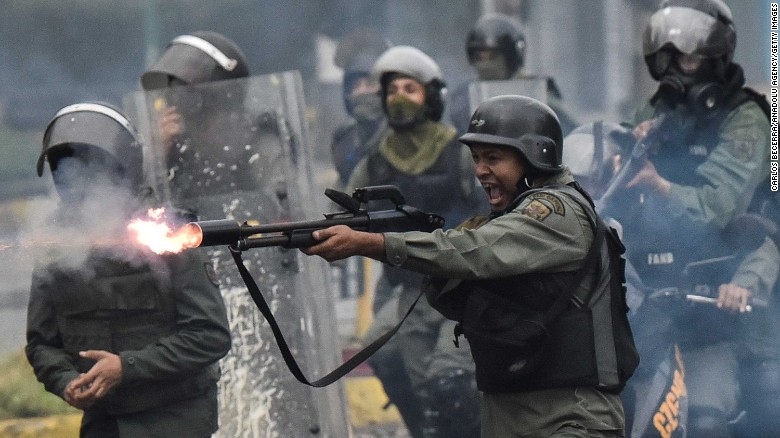 A member of the National Guard fires at protesters during clashes in Caracas on Friday, July 28.