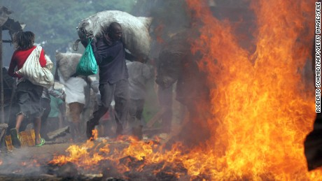 A resident of Kibera runs with a sack of charcoal he stole past a burning shack as he and thousands of other looters swept through the slum ransacking stores and setting cars and other property on fire 31 December 2007.
