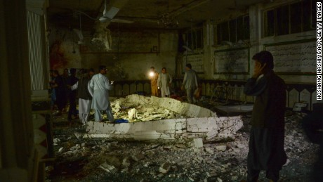 Afghan security personel inspect the site of a suicide bomb attack Tuesday at a Shiite mosque in Herat.