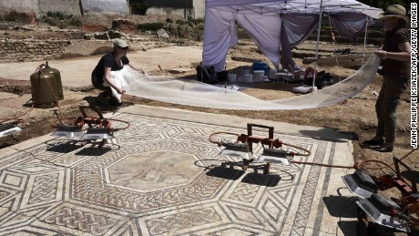 "Archaeologists work on a mosaic on July 31, 2017, on the archaeological antiquity site of Sainte-Colombe, near Vienne, eastern France. Remains of an entire neighbourhood of the Roman city of Vienne have been uncovered in Sainte-Colombe, with lavish residences decorated with mosaics, a philosophy school and shops. The dig of the site, discovered prior to housing construction on a parcel of 5000 m2, began in April 2017 and was due to last six months, but have been extended to December 15, 2017, after the site was classified as an ""exceptional discovery"" by the French Culture Minsitry. / AFP PHOTO / JEAN-PHILIPPE KSIAZEK        (Photo credit should read JEAN-PHILIPPE KSIAZEK/AFP/Getty Images)"
