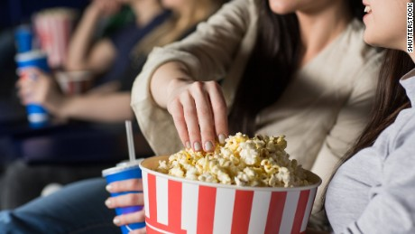 Cropped close up of a woman grabbing popcorn from a bucket watching movies with her female friend at the local cinema food snacks drinks eating enjoyment leisure activity friendship sharing premiere; Shutterstock ID 636925768