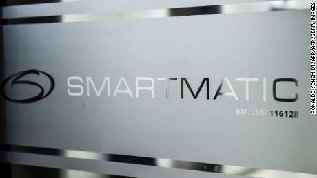 "Picture of the logo of Smartmatic, the firm that supplies Venezuela's voting technology, seen on a sliding door at the headquarters of the company in Caracas, on August 2, 2017. Smartmatic said official figures in Sunday's election of the new super-assembly, with candidates selected from the ruling party, were ""tampered with"" in such a way that the turnout appeared greater than it was. Venezuela's President Nicolas Maduro moved quickly Wednesday to swear in a new assembly with extraordinary powers as he faced charges that turnout figures for the body's election were ""manipulated."" / AFP PHOTO / Ronaldo SCHEMIDT        (Photo credit should read RONALDO SCHEMIDT/AFP/Getty Images)"