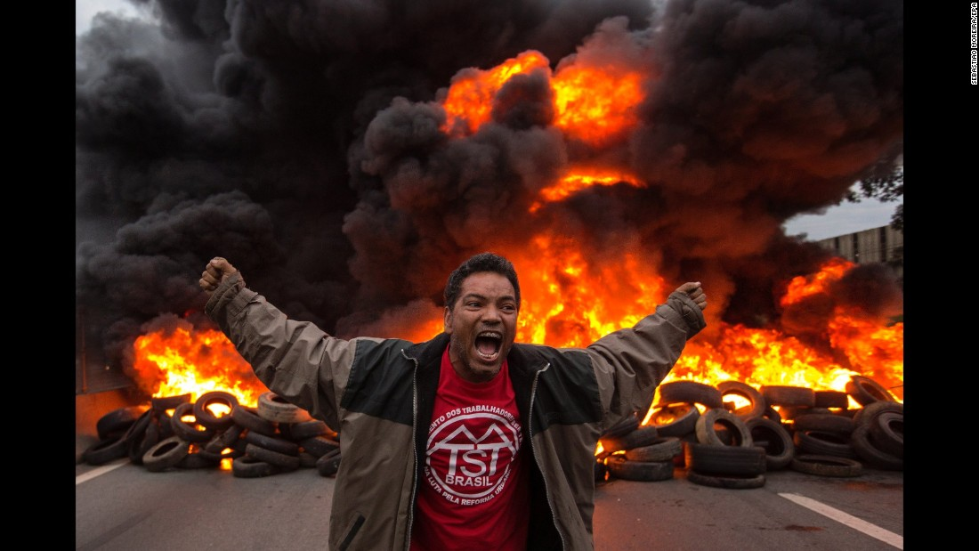 "A man protests in front of burning tires that were blocking a road in Guarulhos, Brazil, on Wednesday, August 2. Protesters were demanding that Brazilian President Michel Temer stand trial after being accused of bribery. Brazilian lawmakers, however, voted to block his prosecution. Temer <a href=""http://www.cnn.com/2017/05/18/americas/brazil-temer-bribery-allegations/index.html"" target=""_blank"">has denied the allegations</a> against him."