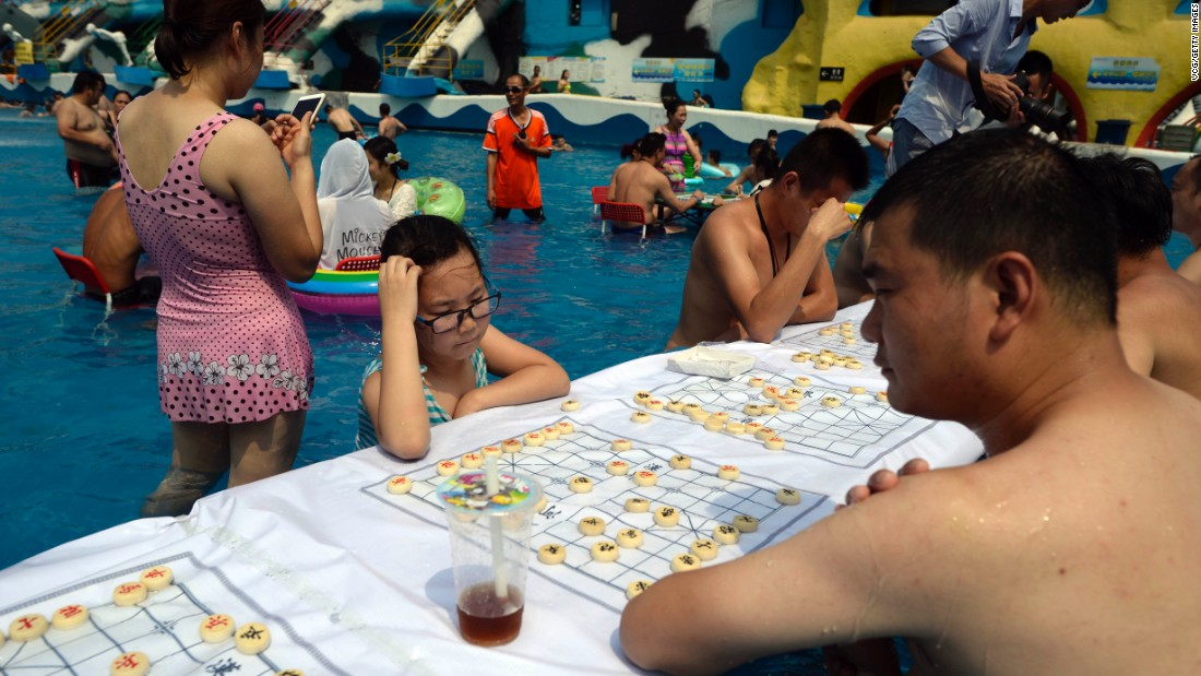 Tourists play chess at a water park in Chongqing, China, on Wednesday, August 2. The city's meteorological observatory had issued a red alert for high temperatures.