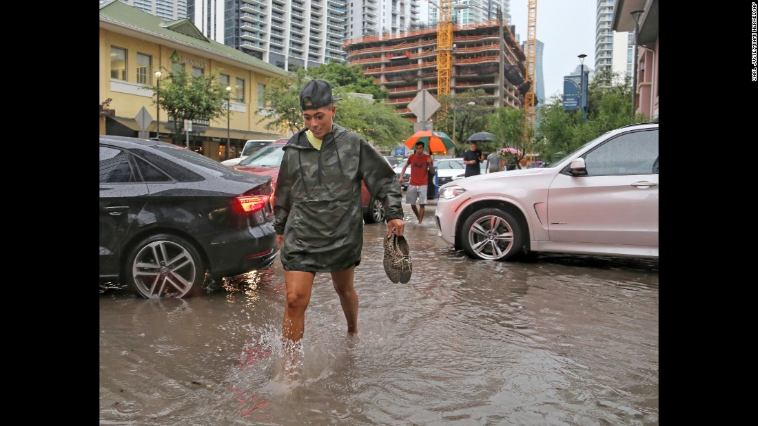 "Pedestrians make their way through flooded streets in the Brickell neighborhood of Miami on Tuesday, August 1. Tropical Storm Emily <a href=""http://www.cnn.com/2017/08/02/us/miami-severe-flooding/index.html"" target=""_blank"">brought heavy rains to the region.</a>"