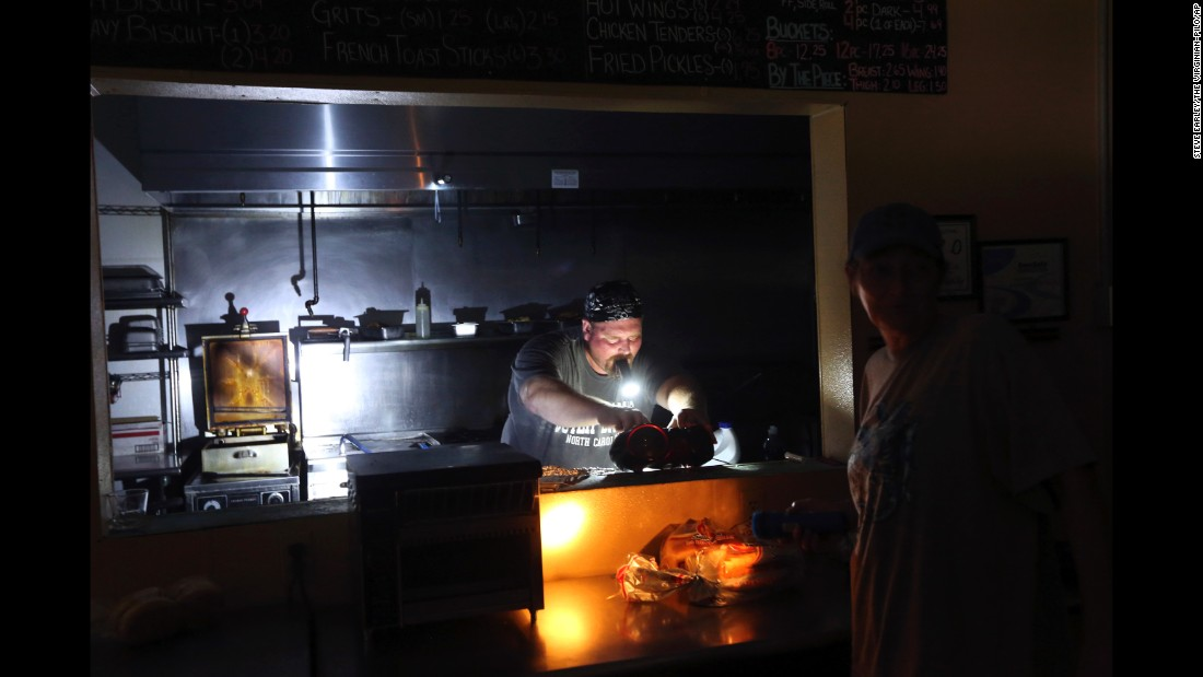 "Aaron Howe cooks in a dark kitchen at the Island Convenience Store in Rodanthe, North Carolina, on Friday, July 28. Thousands of tourists on Ocracoke and Hatteras islands were ordered to pack up and evacuate the area after <a href=""http://www.cnn.com/2017/07/28/us/nc-outer-banks-power-outages/index.html"" target=""_blank"">a major power outage</a> the day before."
