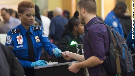 A TSA Agent checks the ID's of passengers as they pass through a security checkpoint on the way to their flights at Reagan National Airport in Arlington, Virginia, December 23, 2015. More than 100 million holiday travelers are expected to travel in the US during the last weeks of the year according to the American Automobile Association. AFP PHOTO / SAUL LOEB / AFP / SAUL LOEB        (Photo credit should read SAUL LOEB/AFP/Getty Images)