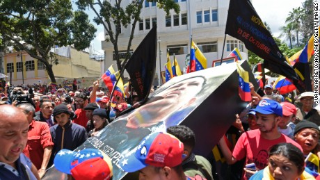 Government supporters carry an image of late Venezuelan President Hugo Chavez during a rally in Caracas on the day of the installation of the Constituent Assembly on August 4, 2017. Venezuelan President Nicolas Maduro was set to install a powerful new assembly packed with his allies Friday, dismissing an international outcry and opposition protests saying he is burying democracy in his crisis-hit country. / AFP PHOTO / JUAN BARRETO        (Photo credit should read JUAN BARRETO/AFP/Getty Images)