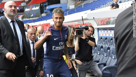 PARIS, FRANCE - AUGUST 04:  Neymar salutes the press after he posed with his new jersey after a press conference with Paris Saint-Germain President Nasser Al-Khelaifi on August 4, 2017 in Paris, France.  Neymar signed a 5 year contract for 222 Million Euro.  (Photo by Aurelien Meunier/Getty Images)