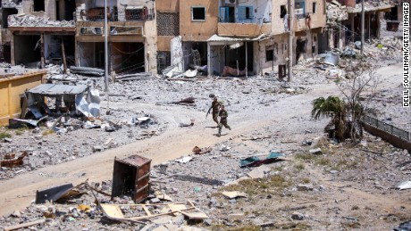 "Members of the Syrian Democratic Forces (SDF) move through destroyed buildings in Raqa on July 28, 2017. The SDF, a US-backed Kurdish-Arab alliance, has ousted Islamic State (IS) group jihadists from half of their Syrian bastion Raqa, where the SDF have been fighting for several months to capture the northern city which has become infamous as the Syrian heart of IS's so-called ""caliphate."""