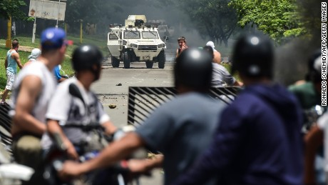 "Anti-government activists and the National Guard clash in Venezuela's third city, Valencia, on August 6, 2016, a day after a new assembly with supreme powers and loyal to President Nicolas Maduro started functioning in the country. In the video posted online earlier, allegedly at an army base used by the National Bolivarian Armed Forces in Valencia, a man presenting himself as an army captain declared a ""legitimate rebellion... to reject the murderous tyranny of Nicolas Maduro"" and demanded a transitional government and ""free elections."" After the video surfaced, military chiefs said troops had put down the ""terrorist"" attack.   / AFP PHOTO / RONALDO SCHEMIDT        (Photo credit should read RONALDO SCHEMIDT/AFP/Getty Images)"