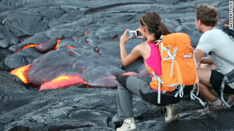 Hawaii lava tourist. Tourists taking photo of flowing lava from Kilauea volcano around Hawaii volcanoes national park, USA.; Shutterstock ID 123043051