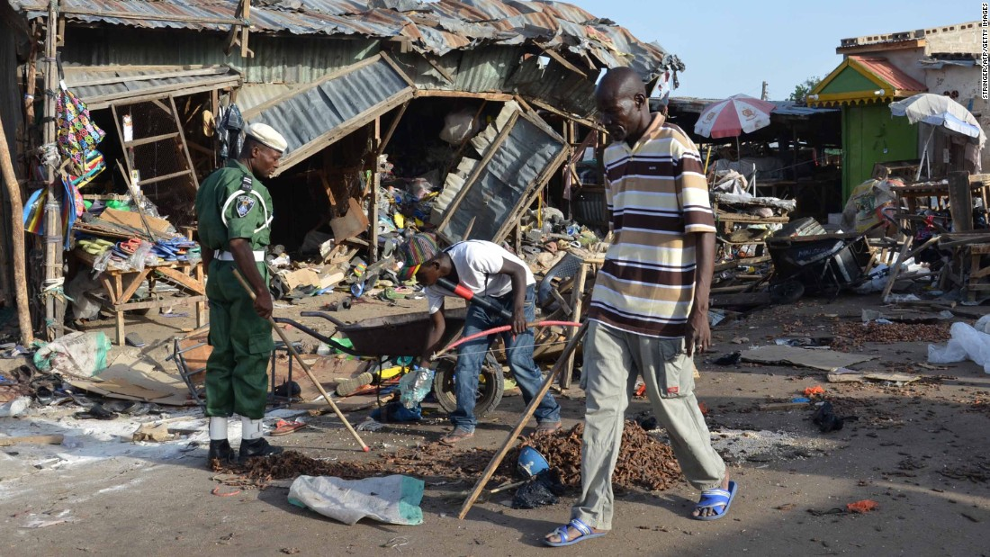 A man walks past the scene of a bombing in Maiduguri. At least 20 people were killed when a young female suicide bomber detonated her explosives at a bus station near a fish market on June 22, 2015.