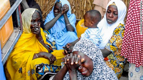 Nigerian women mourn at the site where four female suicide bombers blew themselves up near a bus station in Maiduguri, in the country's northeast, on March 15, 2017, killing two people.