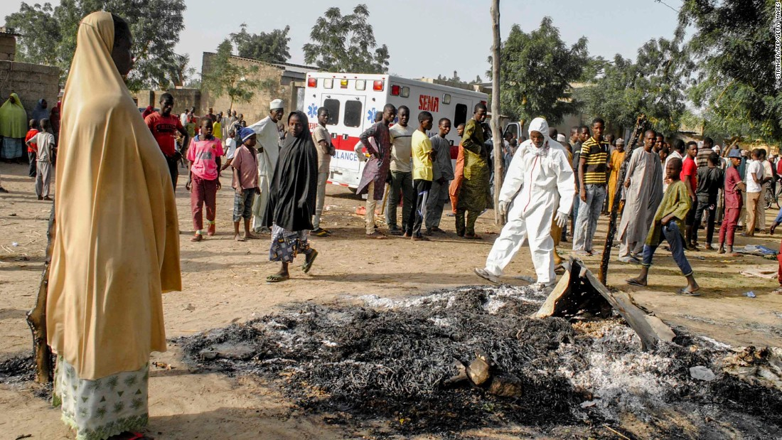 A woman stands at the site where four female suicide bombers blew themselves up near a bus station in Maiduguri on March 15, 2017, killing two people.