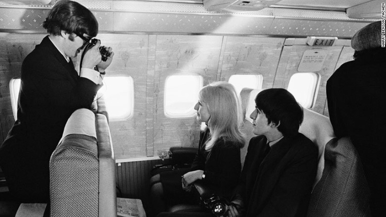 Lennon goes behind the camera to capture Harrison and Lennon's first wife, Cynthia, on route to New York in 1964.